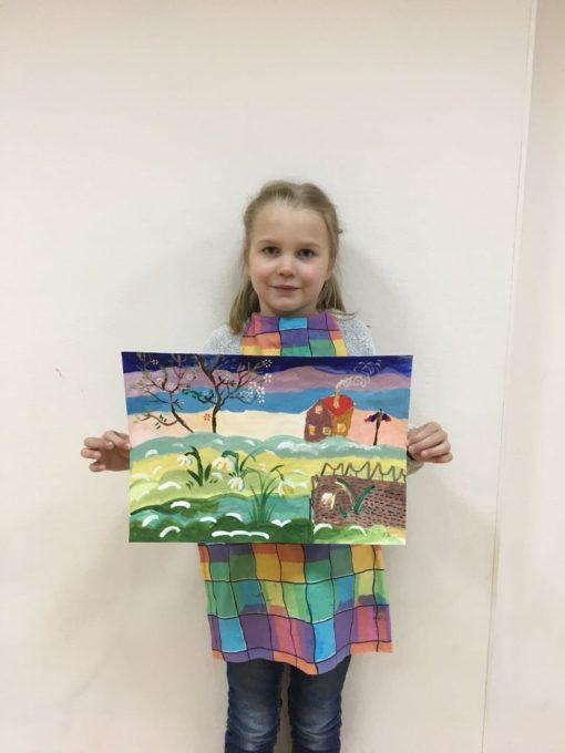 Девочка держит в руках свой цветной рисунок.Март 2018
