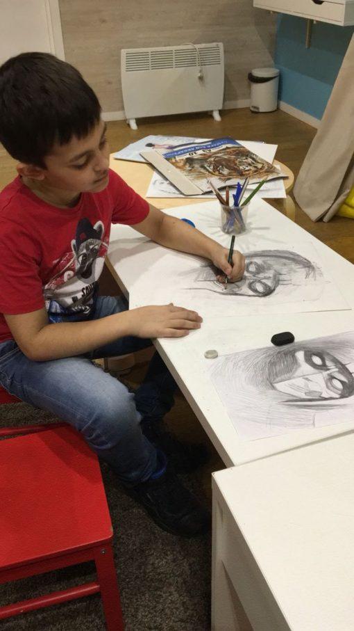 Мальчик рисует лицо монстра из компьютерной игры по нарисованному образцу справа